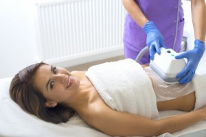 Pretty young woman getting cryolipolyse treatment in cosmetic cabinet